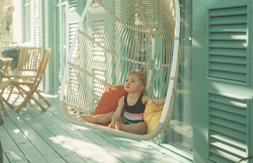 Little child in rocking chair on patio