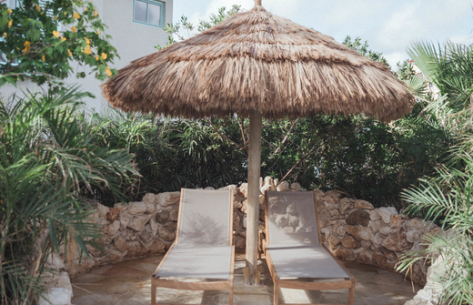 two lounge chairs with palapa in secluded area